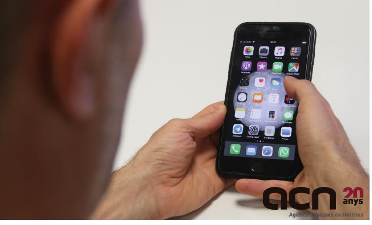 Pla detall d'un treballador mirant el mòbil, l'1 d'agost del 2019. (Foto: ACN)